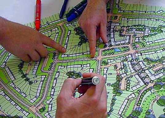 People working on an urban neighbourhood map, pointing out features.